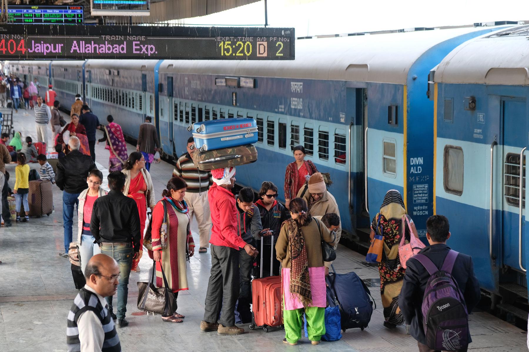 Menschen und ein Zug im Bahnhof von Jaipur.