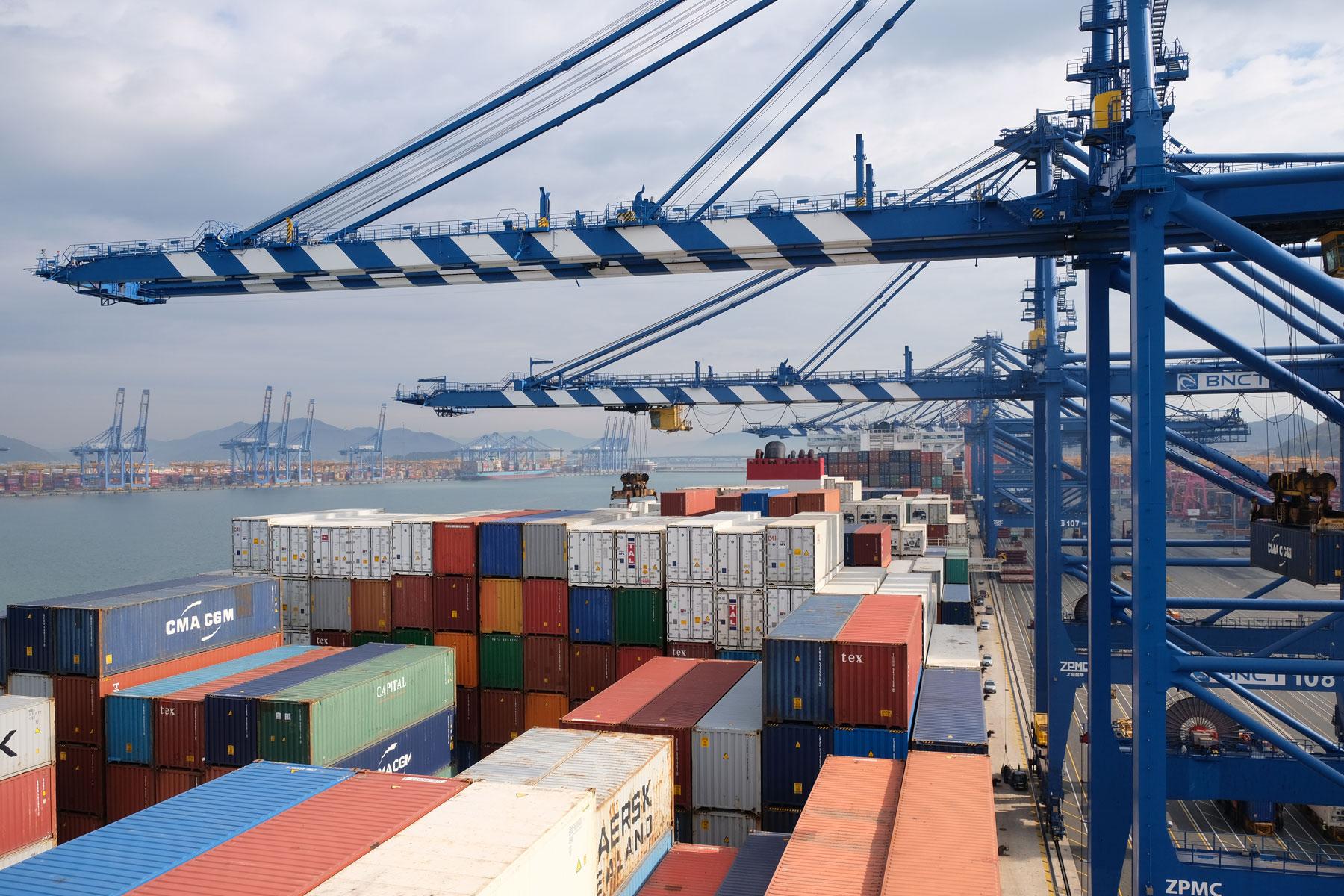 Kräne stehen über dem im Hafen liegenden Containerschiff.