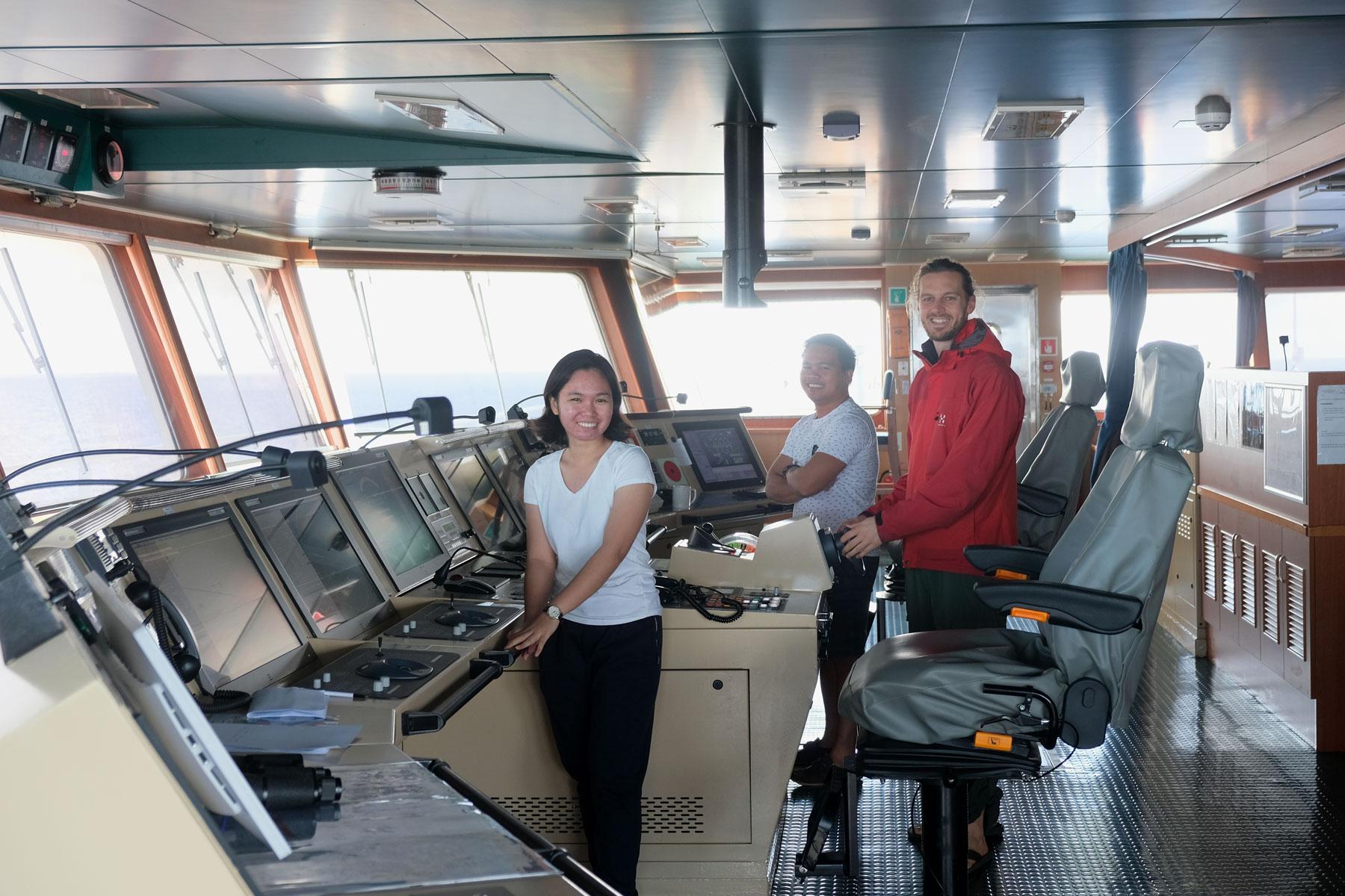 Sebastian steht mit zwei Offizieren auf der Brücke eines Containerschiffs.