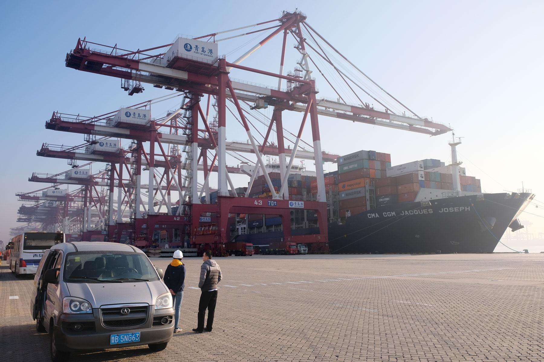 Leo und der Hafenagent stehen vor dem Containerschiff.