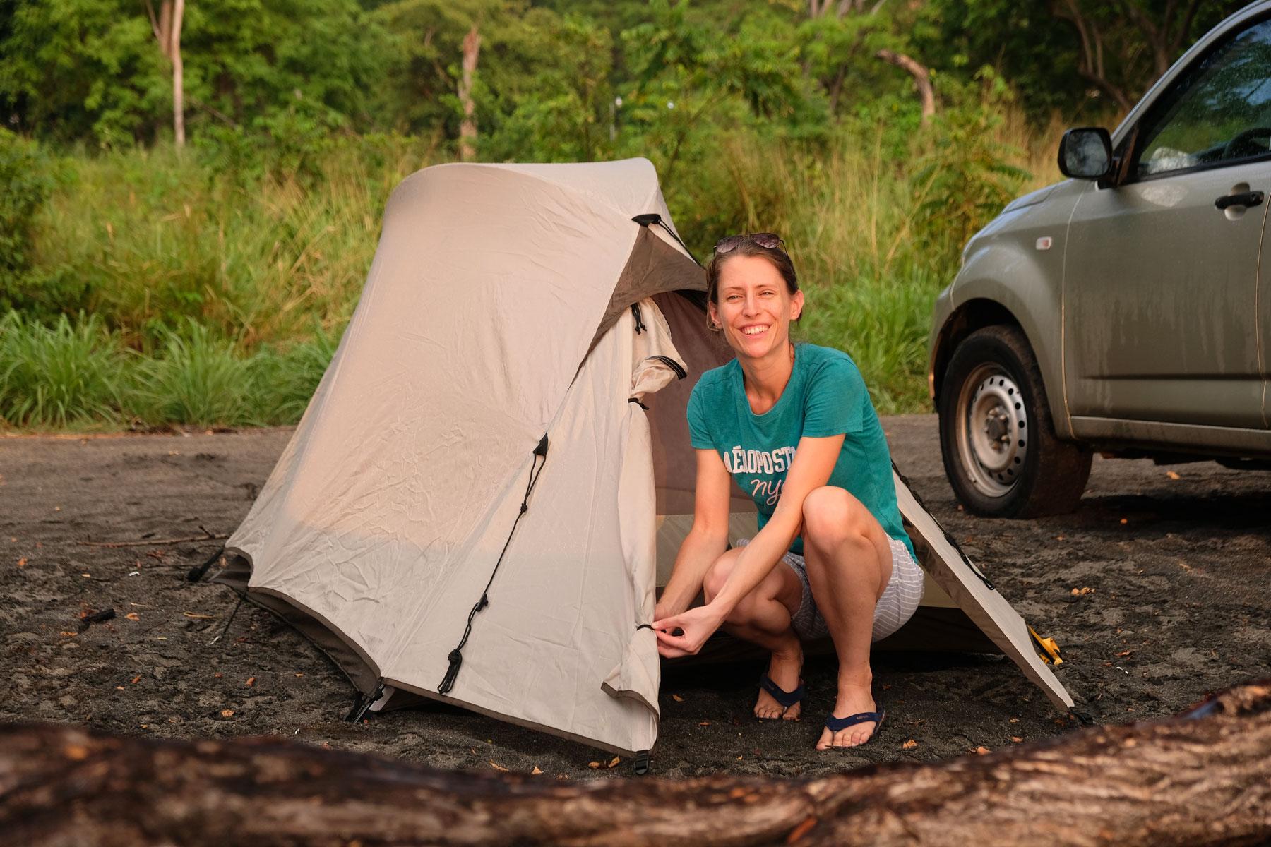 Leo kniet vor einem kleinen Zelt am Strand von Costa Rica.