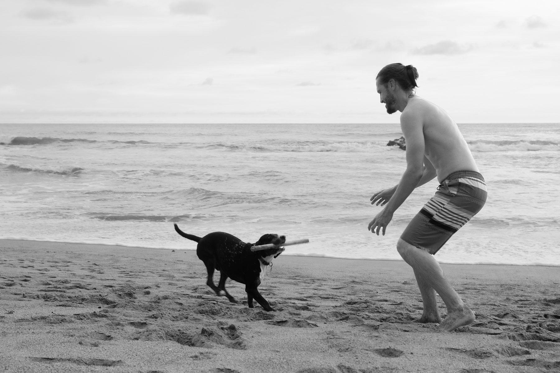 Sebastian spielt mit unserem House Sitting Hund Max am Strand von Costa Rica.