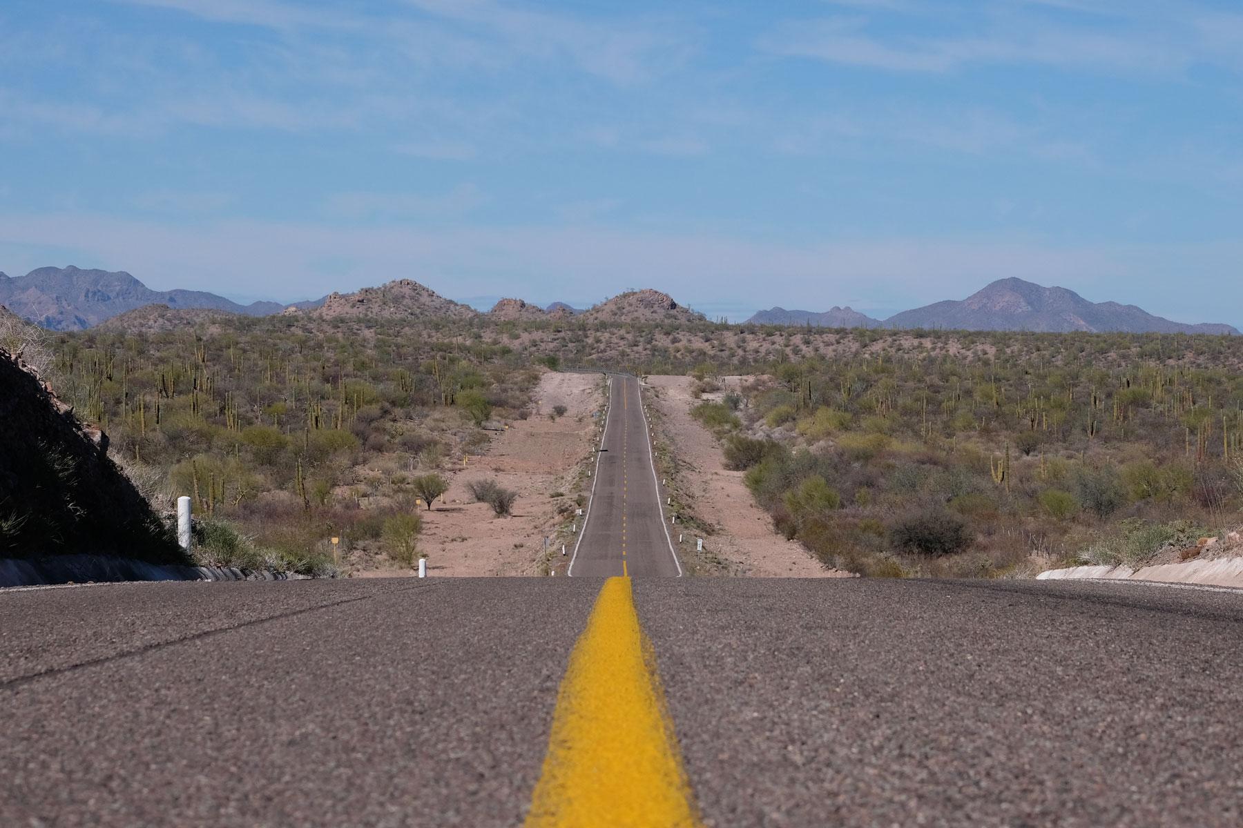 Eine Straße zieht sich durch die Weite der Baja California in Mexiko.