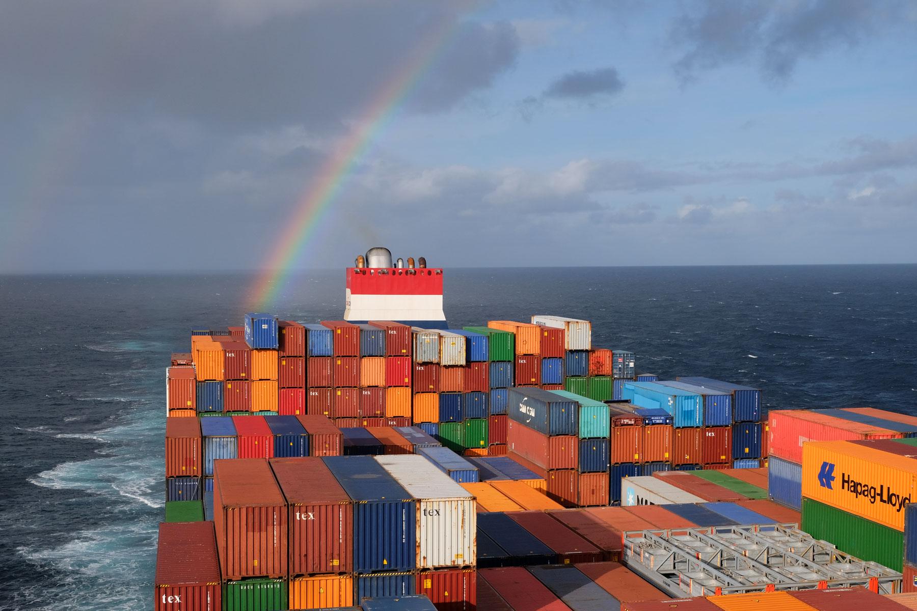 Hinter unserem Containerschiff leuchtet ein Regenbogen über dem Atlantik.
