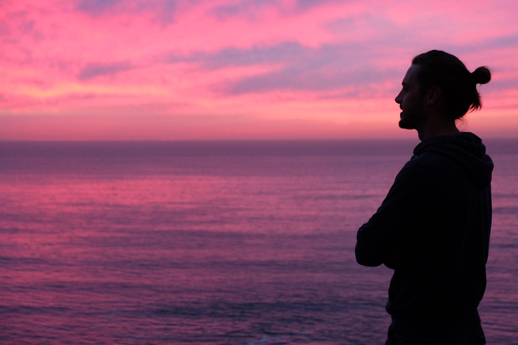 Sebastian steht vor einem lila verfärbten Abendhimmel am Meer.