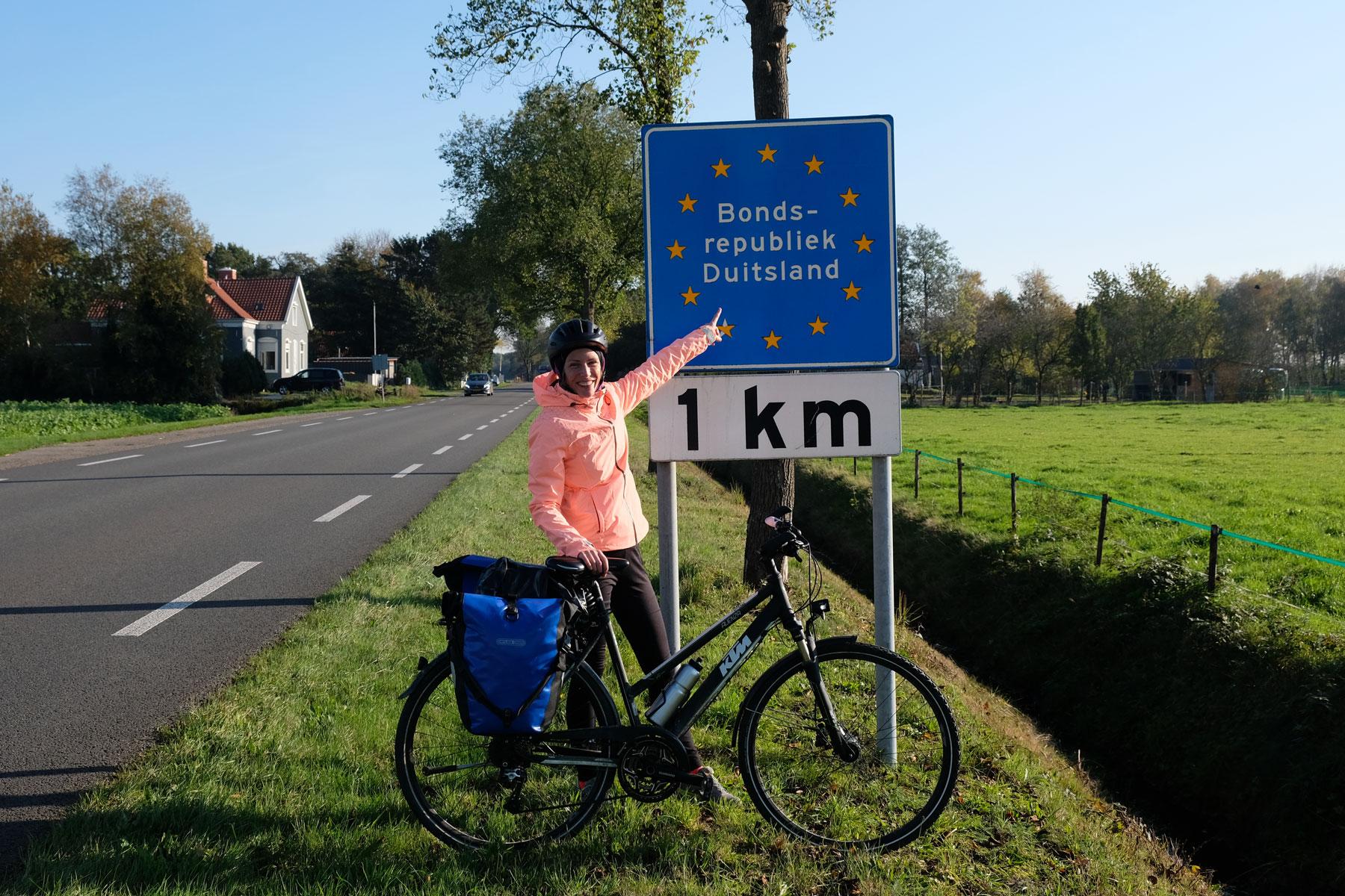 """Leo steht mit ihrem Fahrrad vor einem Schild """"Bundesrepublik Deutschland - 1 km""""."""