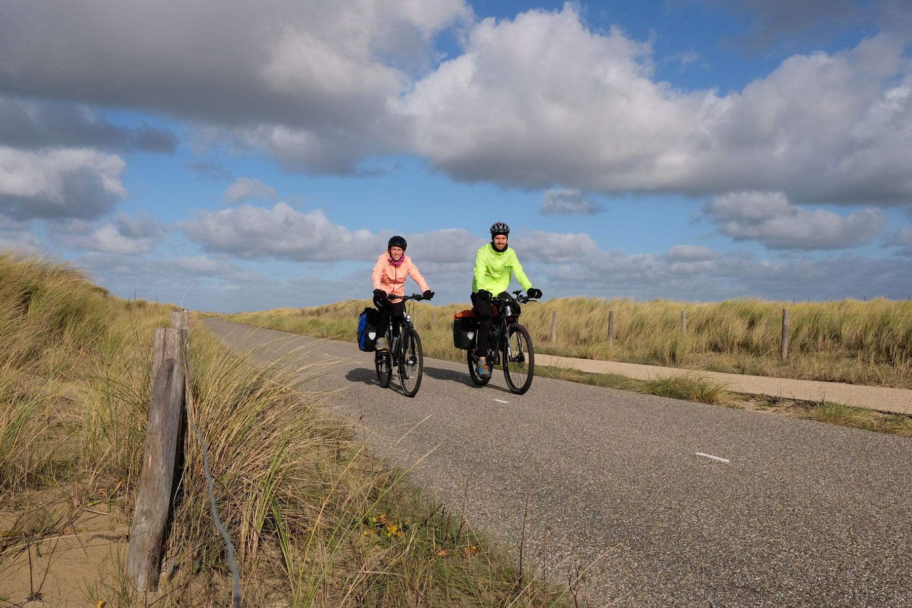 Leo und Sebastian fahren mit ihren Fahrrädern durch die Dünen der Niederlande.