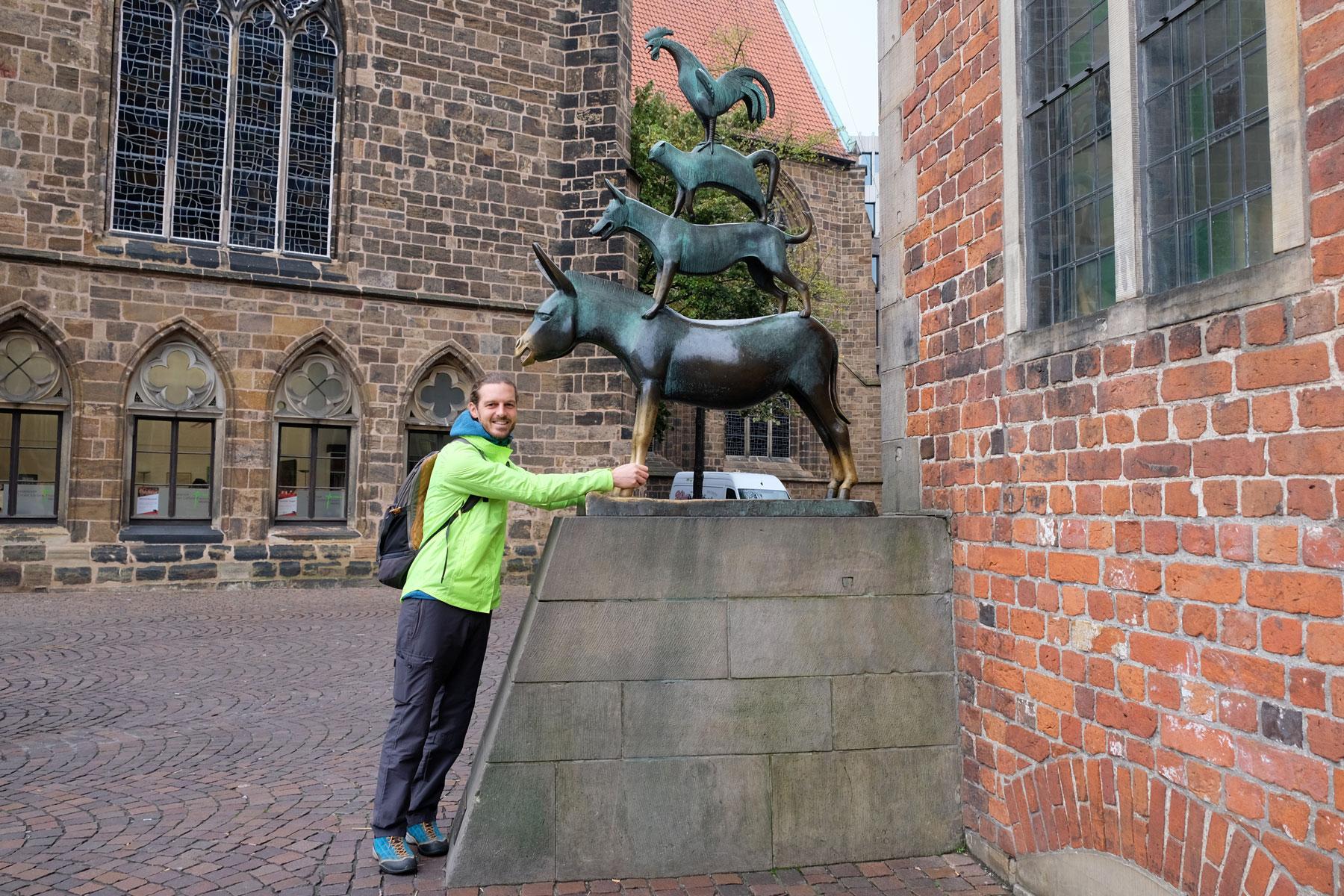 Sebastian umgreift die Vorderbeine des Esels der Bremer Stadtmusikanten.
