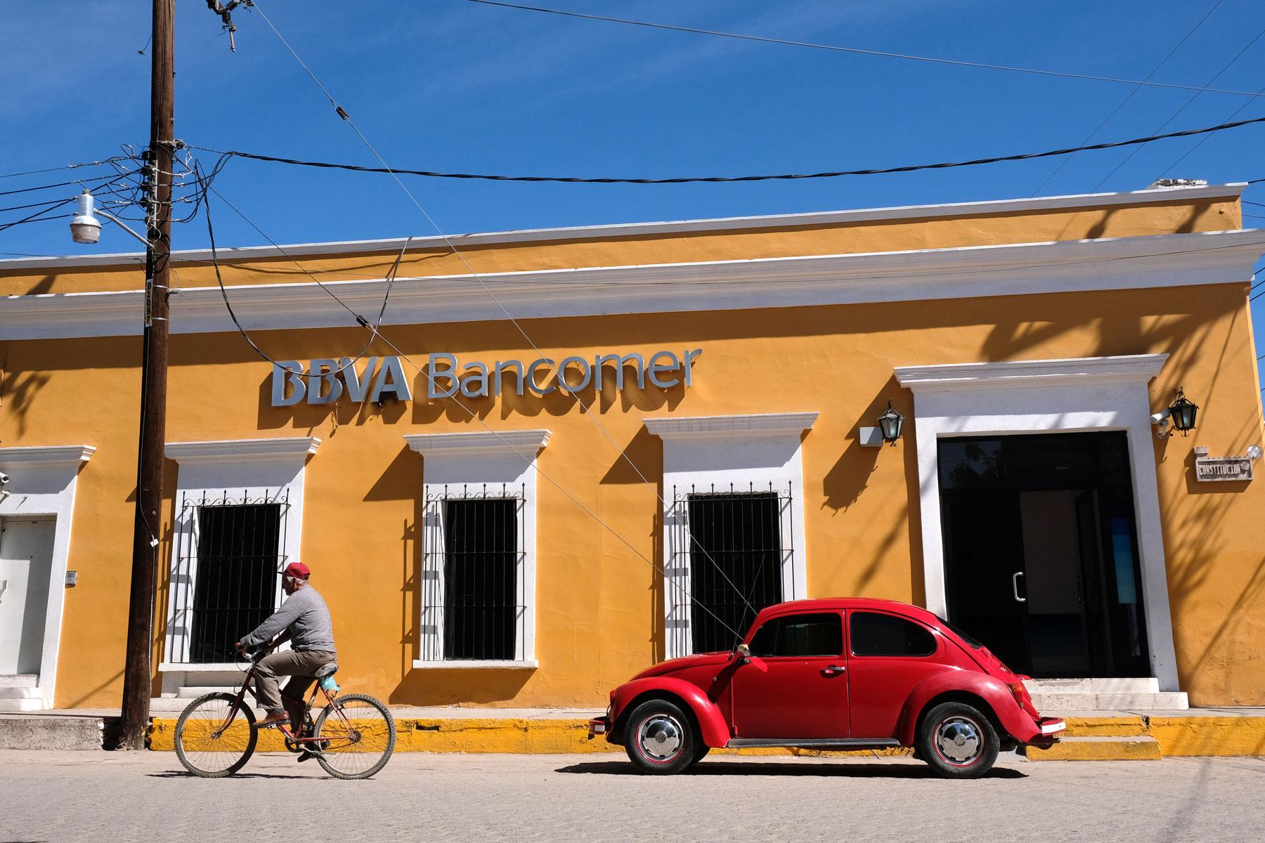 Ein roter VW-Käfer steht in El Fuerte in Mexiko vor einem gelben Haus.