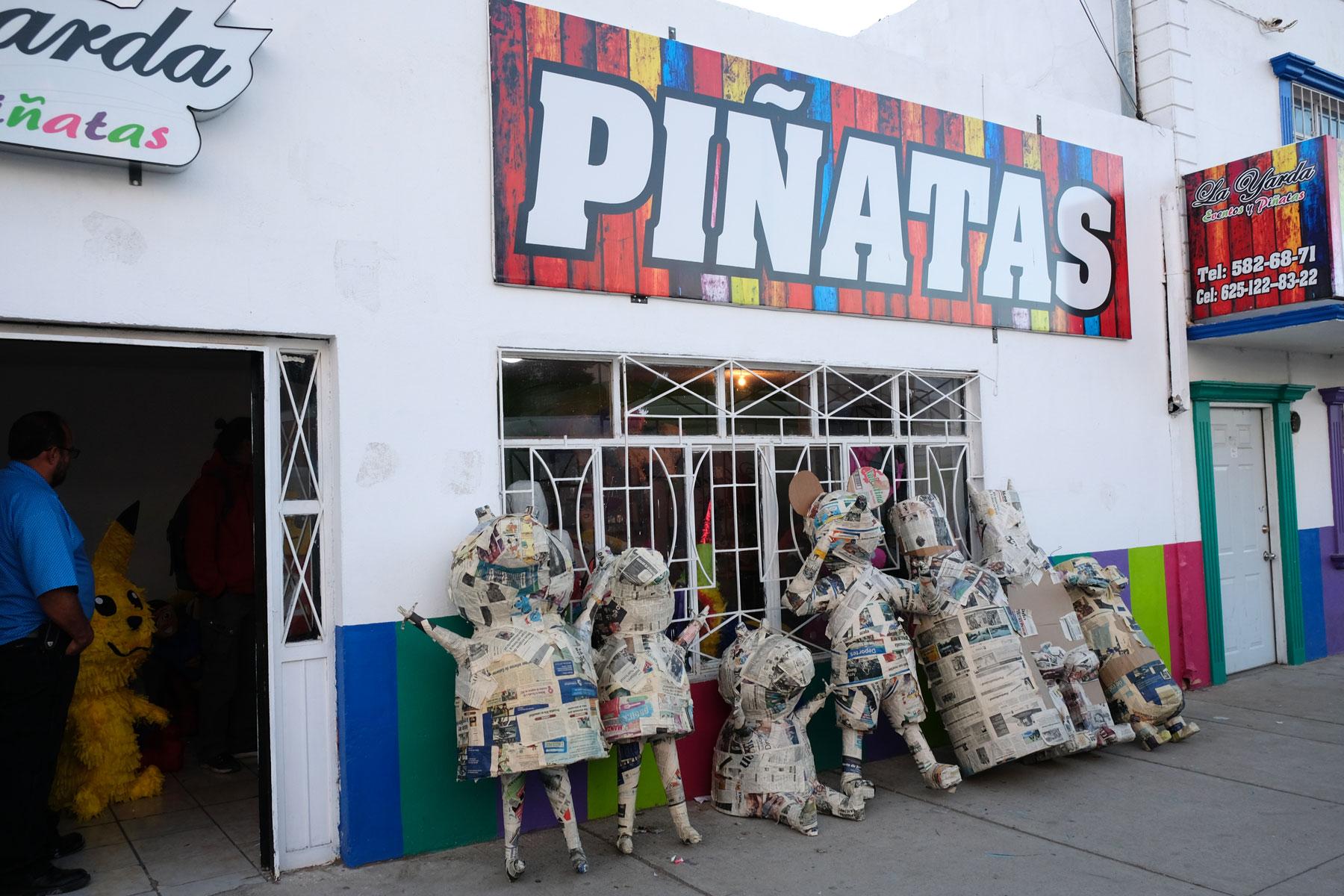 Vor einem Geschäft in Mexiko stehen Pappmachéfiguren.