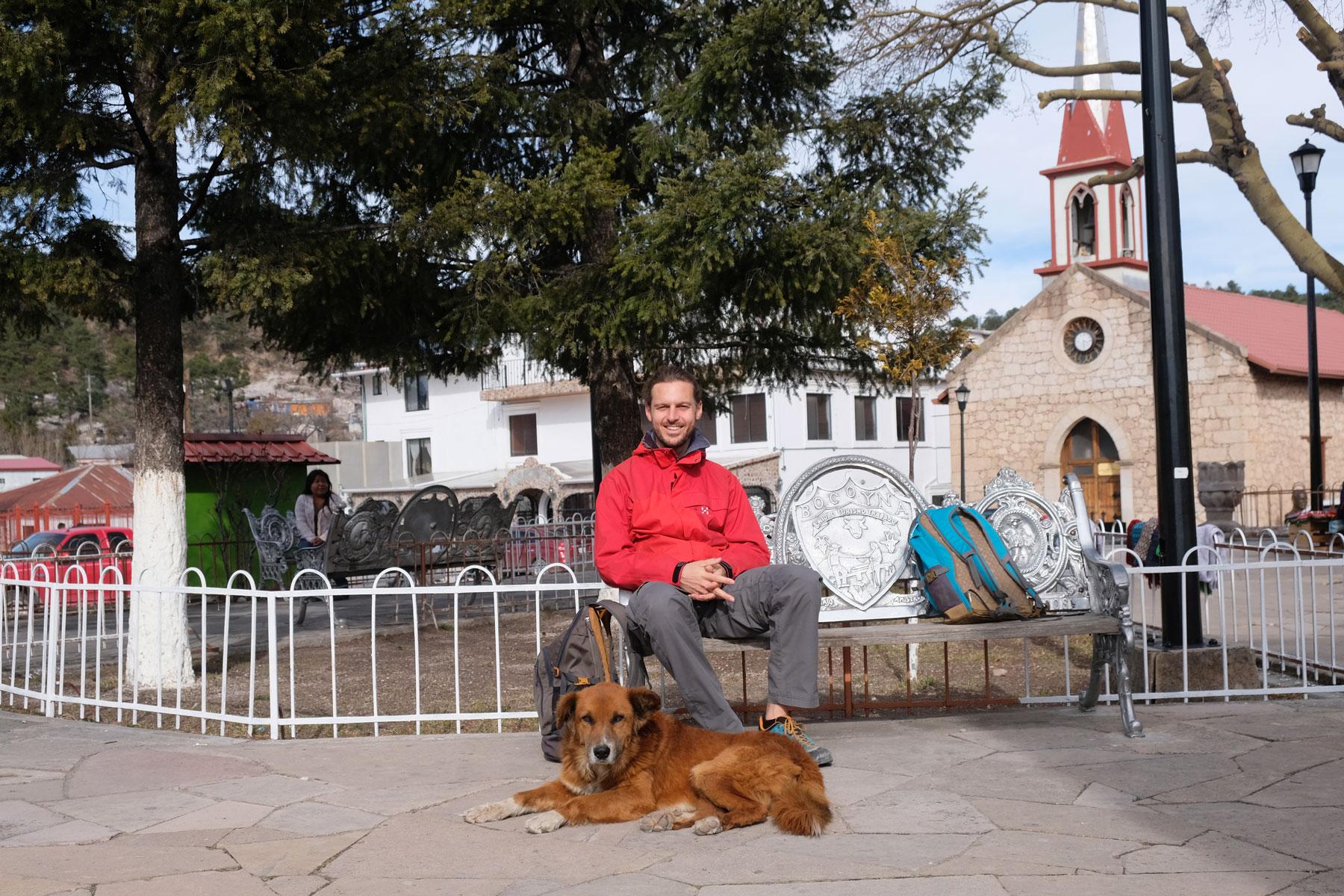 Sebastian und ein Straßenhund sitzen auf der Plaza von Creel in Mexiko.