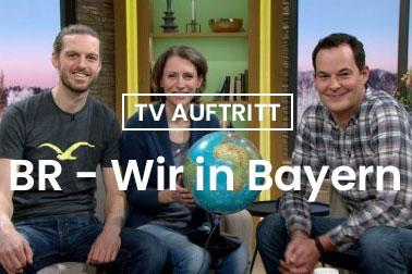 Sebastian Ohlert und Leonore Sibeth sitzen mit dem Moderator Dominik Pöll in der Fersehsendung Wir in Bayern des Bayerischen Rundfunks.