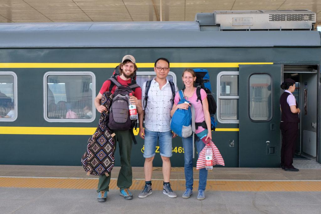 Sebastian und Leo stehen mit einem Chinesen vor einem Zug.