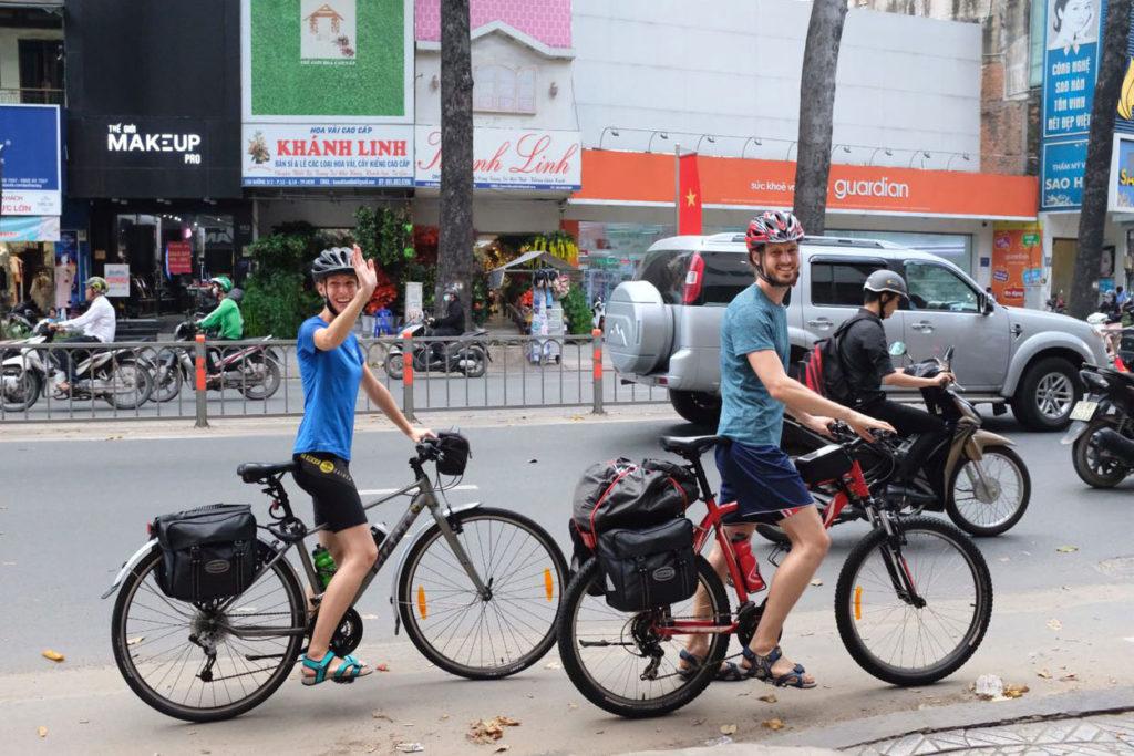Leo und Sebastian sitzen auf ihren Fahrrädern und winken zum Abschied.