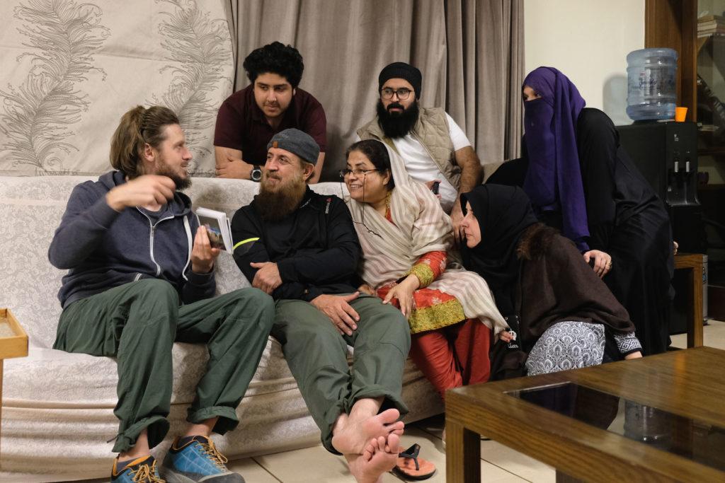 Sebastian zeigt einer pakistanischen Familie ein Fotoalbumb mit Bildern aus Deutschland.