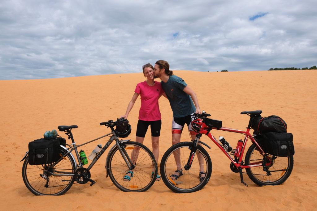 Leo und Sebastian stehen mit ihren Fahrrädern auf einer Sanddüne in Vietnam.