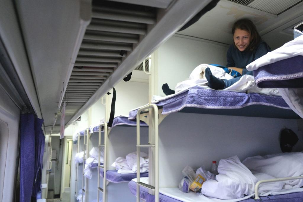 Leo sitzt im Bett eines Nachtzuges in China.